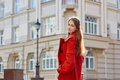 Young beautiful woman in red coat in the city Stock Photography