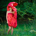 Young beautiful woman in red dress in green woods Royalty Free Stock Photography