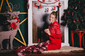 Young beautiful woman in a red warm pajamas with scandinavian ornaments sitting near decorative fireplace and drinking hot tea Royalty Free Stock Photo