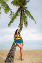 Young beautiful woman relaxing under the palm tree on a tropical Royalty Free Stock Photo
