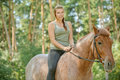 Young beautiful woman rides horse portrait of brunette riding at summer green forest Royalty Free Stock Images
