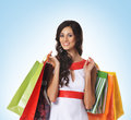 A young beautiful woman with shopping bags and brunette posing the image is taken on blue background Stock Photography