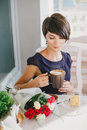 Young beautiful woman with short hair drinking steaming coffee in a street cafe Stock Photos