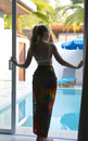 Young beautiful woman silhouette is on the threshold of a country house at an exit in pool Stock Photos