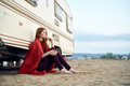 Young beautiful woman sits on a beach near a trailer, sea, vacation