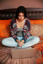 Young beautiful woman sitting on the bed and looking at laptop Royalty Free Stock Images