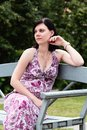 Young beautiful woman sitting on bench in city park. Pretty russian girl outdoors Royalty Free Stock Photo