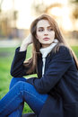 Young beautiful woman sitting on a grass in sun light on sunset Royalty Free Stock Photo