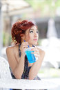 Young beautiful woman sitting at outdoor cafe holding soft drink 图库摄影