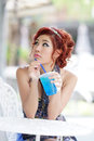 Young beautiful woman sitting at outdoor cafe holding soft drink glass model is thai ethnicity Stock Photography