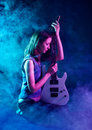 Young beautiful woman is sitting on stage with a guitar . Fog on Stock Photos