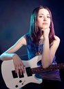 Young beautiful woman is sitting on stage with a guitar . Fog on Royalty Free Stock Images