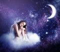 Young beautiful woman sleeping on a fairy cloud in a starry night sky in the moonlight Royalty Free Stock Photography