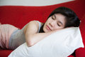 Young beautiful woman sleeping on red sofa Royalty Free Stock Images