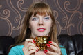 Young beautiful woman smiles and holds gilt cup on couch in room Royalty Free Stock Photography