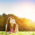 Young beautiful woman smiling and lying on grass the at summer sunset looking at the sky natural happiness fun harmony Royalty Free Stock Images