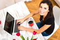 Young beautiful woman smiling while using a laptop at home being cheerful computer Stock Photography