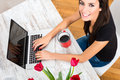 Young beautiful woman smiling while using a laptop at home being cheerful computer Stock Photo