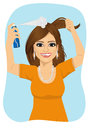 Young beautiful woman spraying her hair with dry shampoo