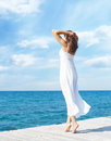Young beautiful woman standing on a pier at summer.  Vacation, t Royalty Free Stock Photo