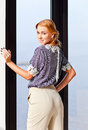 Young beautiful woman in striped blouse the before a window Stock Images