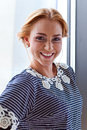 Young beautiful woman in striped blouse the before a window Royalty Free Stock Photos