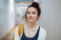 young beautiful woman student with pencils in hair bun, standing in hall of college university Royalty Free Stock Photo