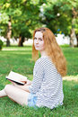 Young beautiful woman in summer park reading book Stock Photo