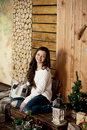 Young beautiful woman in sweater and blue jeans sitting on floor at home Royalty Free Stock Photo