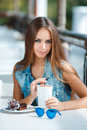 Young beautiful woman at a table in summer cafe Royalty Free Stock Photo