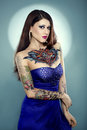 Young beautiful woman with tattoos tattooed girl in blue dress Stock Photo