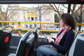 Young beautiful woman in tourist bus near prado listens tour program madrid spain Royalty Free Stock Image