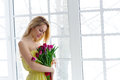 Young beautiful woman with tulip bunch in yellow dress. 8 march international womens day. Royalty Free Stock Photo