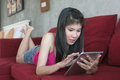 Young beautiful woman using computer tablet on red sofa smiling Royalty Free Stock Images
