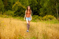 Young beautiful woman walking in a field, summer outdoors Royalty Free Stock Photo