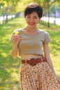 Young beautiful woman wearing simply skirt clothes standing in park with yellow flowers in hand Stock Photo