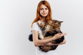 Young beautiful woman on white isolated background holds a cat