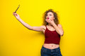 Young beautifulgirl with an curly hairstyle send selfie kisses. Laughing girl take selfie from phone on Yellow background. Royalty Free Stock Photo