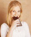 Young beauty blond teenage girl eating chocolate Royalty Free Stock Photo