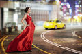 Young beauty famous woman in fluttering red dress outdoor on the big city street Royalty Free Stock Photos