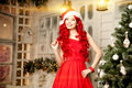 Young beauty smiling santa woman near Christmas tree. Fashionabl Royalty Free Stock Photo