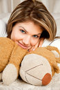 Young beauty woman in the bed with teddy bear Royalty Free Stock Photo