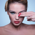 Young beauty woman covering one eye with her fingers red manicure Royalty Free Stock Images