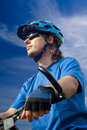 Young biker in helmet on a blue sky background Stock Image