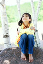 Young biracial girl sitting on rock under trees quietly outdoors in summer peaceful scene Royalty Free Stock Images