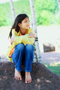 Young biracial girl sitting on rock under trees quietly outdoors in summer peaceful scene Stock Photo