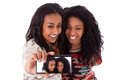 Young black african american teenage girls taking pictures with cell phone isolated on white background people Royalty Free Stock Photo