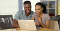 Young black couple browsing internet on laptop together in the living room Royalty Free Stock Photo