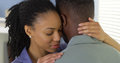 Young black couple embracing each other at home Stock Images
