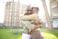 Young black couple hugging in a park at sunset while visiting london city Stock Images